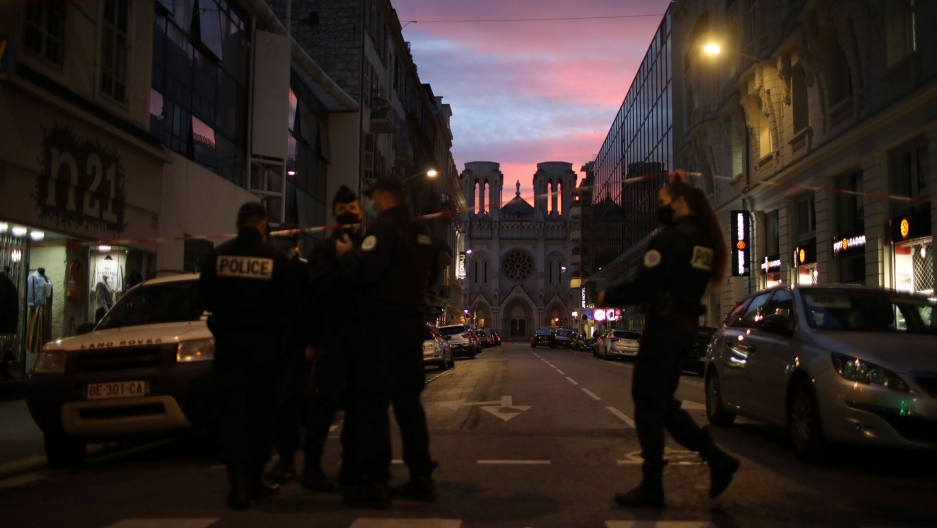 Several police are shown at the end of a street with the Notre Dame church in the distance and the sun setting.