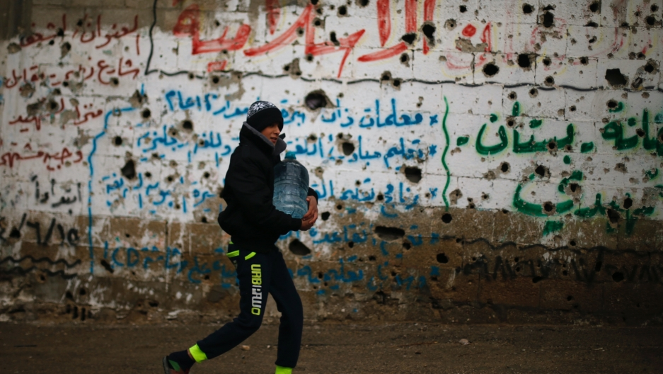 A boy carries a tub of water down a street past a wall full of grafitti in Arabic letters.