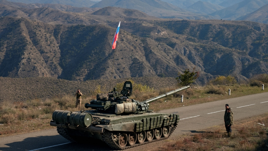 Service members of Russian peacekeeping troops stand next to a tank near the border with Armenia, following the signing of a deal to end the military conflict between Azerbaijan and ethnic Armenian forces, in the region of Nagorno-Karabakh, Nov. 10, 2020.