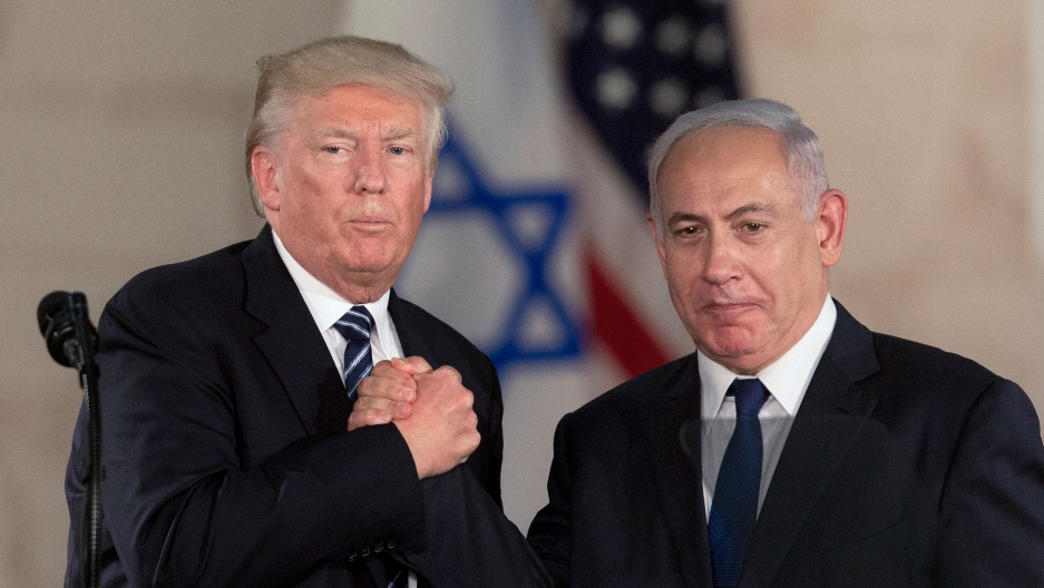 US President Donald Trump and Israeli Prime Minister Benjamin Netanyahu are shown both wearing dark suits and in a tight handshake.