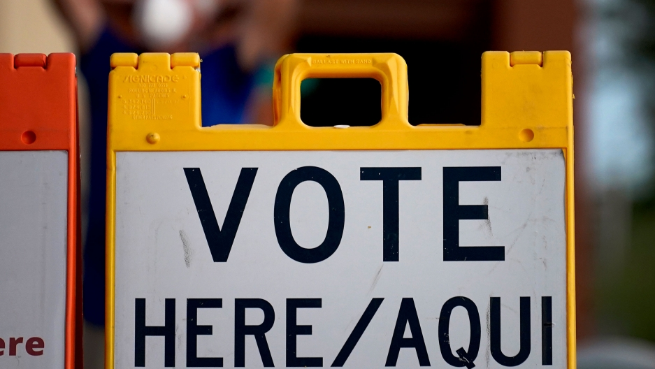 "A plastic yellow sign is shown with ""Vote Here/Aqui"" printed on it."