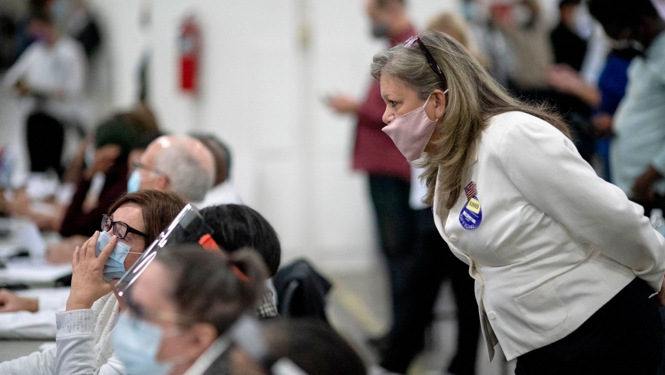 A woman wearing a white blazer and face mask is shown looking over the shoulder of a row of seated election inspectors.