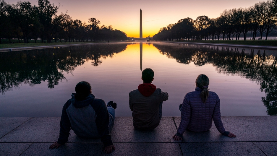 Three people are shown sitting on the ground in front of a long reflecting pool with the Washington Monument in the distance as the sun comes up.