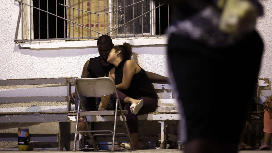 In this photo from July 28, 2019, a woman from Nicaragua embraces a man from Africa under the patio floodlights at El Buen Pastor shelter for migrants in Ciudad Juárez, Mexico.