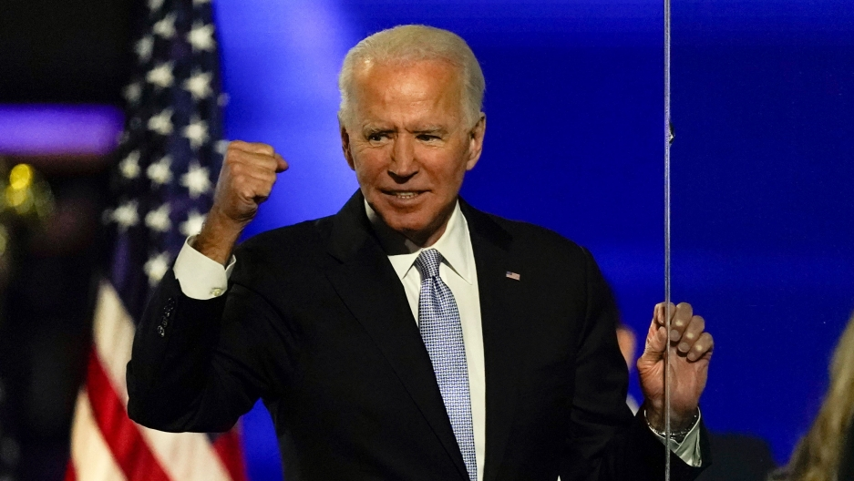 President-elect Joe Biden is shown wearing a dark suit and smiling while holding his fist in the air.