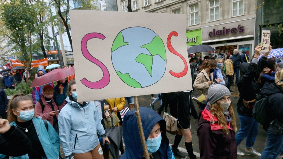 A protester holds a sign that reads SOS among other protesters on a street in Austria.