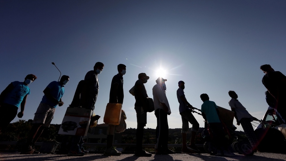 Refugees and migrants are shown in shadow standing in a lin carrying various belongings with the sun flaring in the distance.