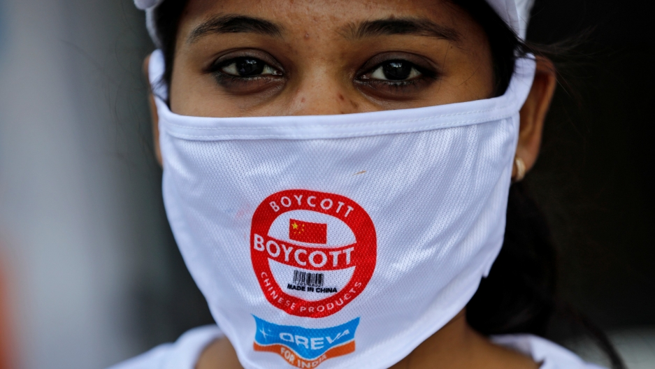 A demonstrator wearing a protective face mask with a message attends a protest demanding to boycottChina-made products.