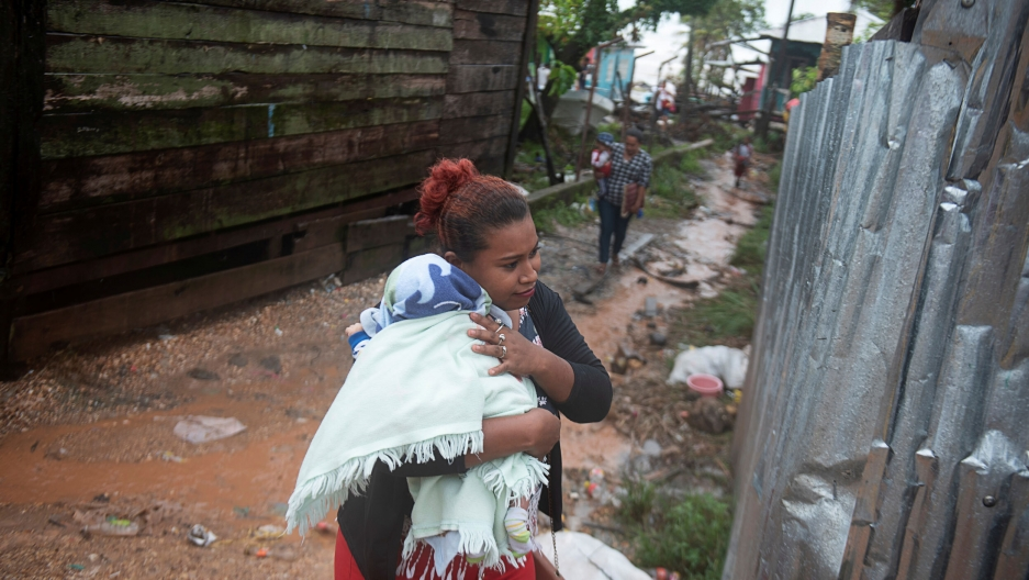 A woman protects her baby from the rain as Hurricane Iota approaches Puerto Cabezas, Nicaragua, Nov. 16, 2020.