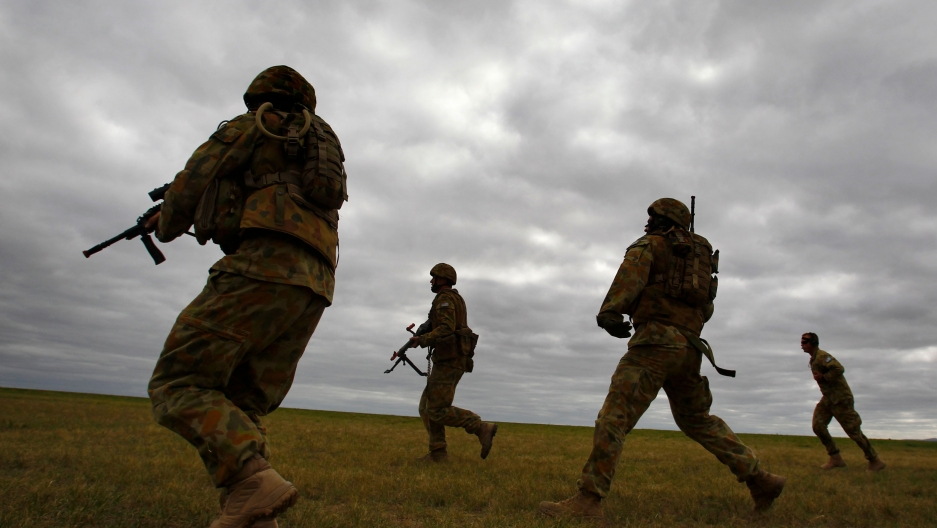 A group of four soldiers are shown walking across a field wearing full battlefield fatigues and carrying weapons.