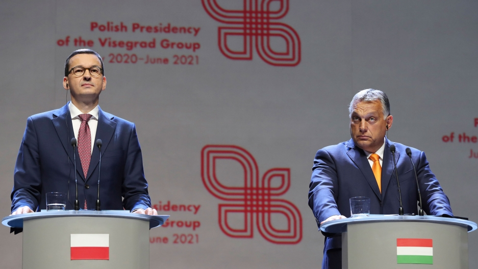 Viktor Orban (R) prime minister of Hungary and Polish Prime Minister Mateusz Morawiecki are shown both wearing dark suits and standing behind podiums, each with their respective country flags on the front.