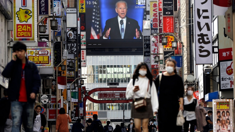 The busy streets of the Shinjuku shopping district in Tokyo adorned with signs for stores and restaurants lining either side while a live broadcast shown on a large public television monitor of President-elect Joe Biden.