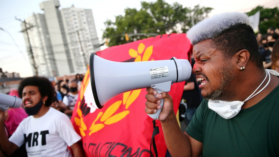 A demonstrator reacts during a protest against racismafter João Alberto Silveira Freitaswas beaten to death by security guards at a Carrefour supermarket in Porto Alegre, Brazil, Nov.23, 2020.