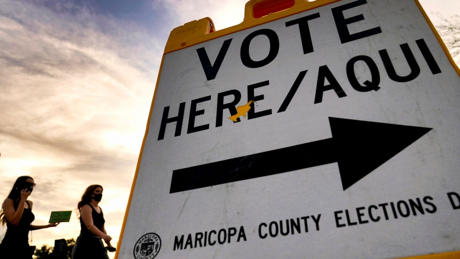"""A sign that has """"Vote here/Aqui"""" printed on it is shown in the nearground with two woman walking in the background."""