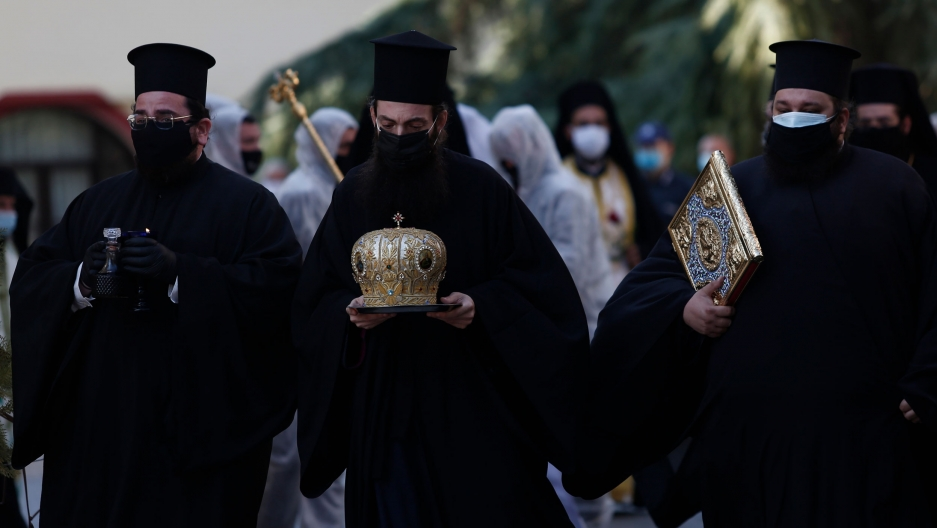 Three priests are shown wearing face masks and dressed in traditional black Greek Orthodox attire while carrying religious objects.