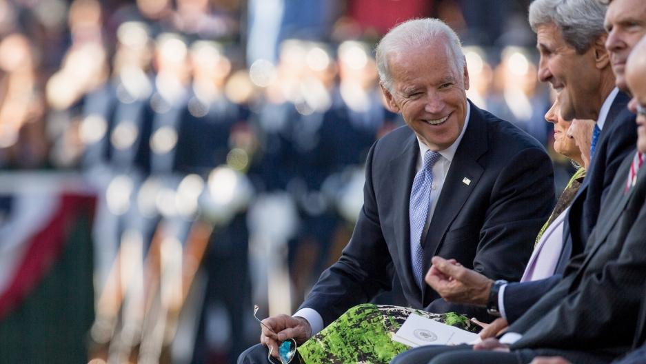 Joe Biden sitting next to John Kerry at an event in 2015