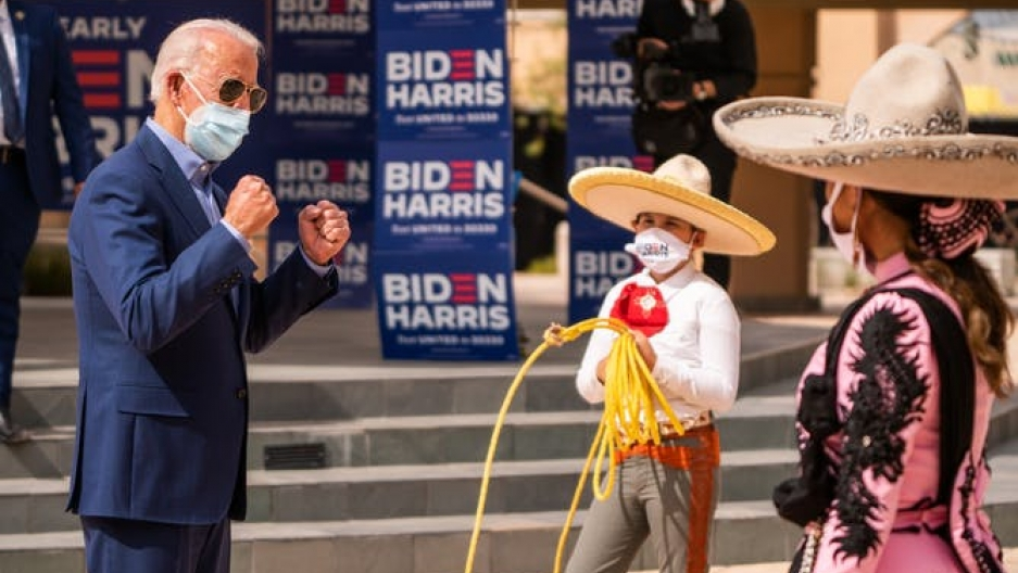 Joe Biden interacts with two Latinos wearing sombreros and Biden/Harris masks.
