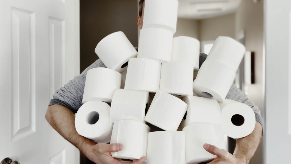 A man holds a large stack of toilet paper rolls.