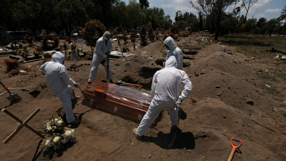 Four people are shown on holding ropes on each corner of a brown wooden coffin in a row with several dug out graves awaiting future burials.