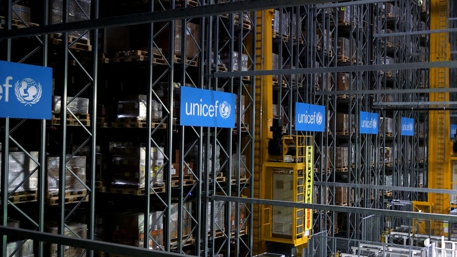Rows of tall storage columns are show in a UNICEF warehouse.