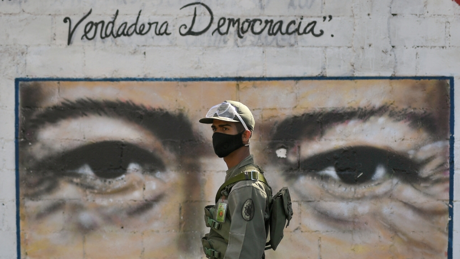 A soldier is shown wearing a face mask and a military uniform while standing in front of a wall painted with the eyes of the late President Hugo Chávez.