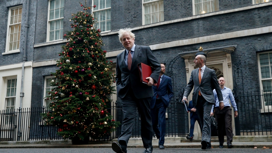 British Prime Minister Boris Johnson is shown wearing a suit and walking with a red folder under his arm and a large Christmas tree in the background.