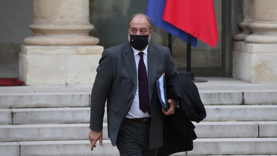 French Justice Minister Eric Dupond-Moretti is shown wearing a dark-colored face mask and gray suit while carrying a folder.