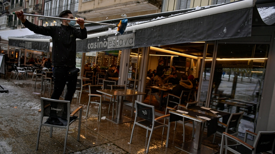A worker wearing a face mask clears snow from the roof of a bar, in Pamplona, northern Spain, Dec. 5, 2020.
