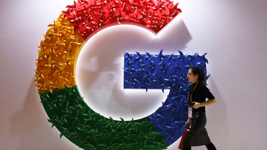 A woman wearing a skirt and name badge walks past the logo for Google affixed to the wall.