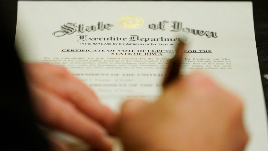 A member of Iowa's Electoral College signs the Certificate of Vote of Electors for the State of Iowa at the Statehouse in Des Moines, Iowa, Dec. 14, 2020.