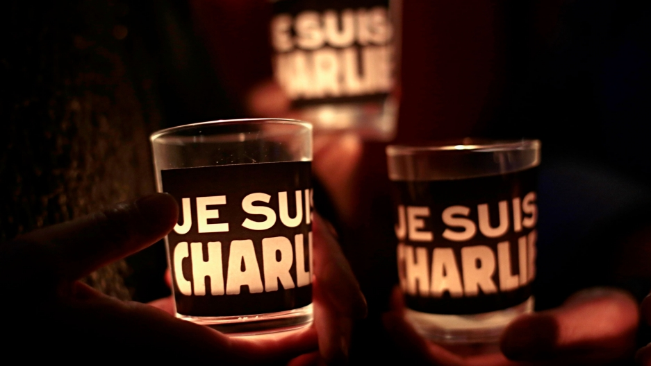 In a photograph taken in the dark, three glasses with candles glowing inside are shown with the phrase 'Je Suis Charlie' printed on it.