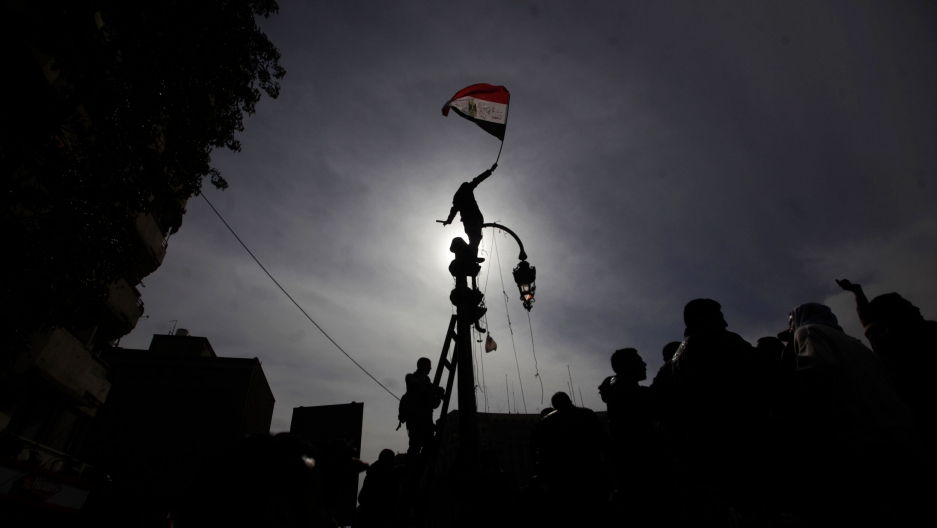 A protester is shown standing on top of a street light and holding the Egyptian flag while blocking the sun and creating a shadow.