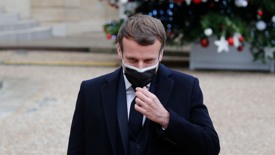 French President Emmanuel Macron is shown wearing a face mask and dark suit while standing outside.
