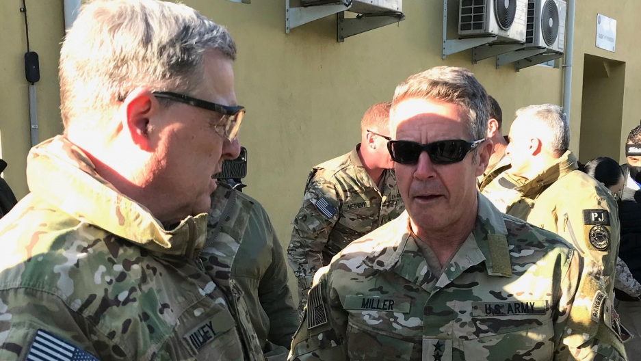 Gen. Mark Milley and Gen. Scott Miller are shown facing each other and wearing military fatigues.