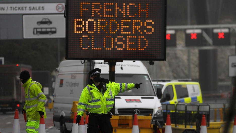 A police officer directs traffic at the entrance to the closed ferry terminal in Dover, England, after the Port of Dover was closed and access to the Eurotunnel terminal suspended following a French government's announcement.