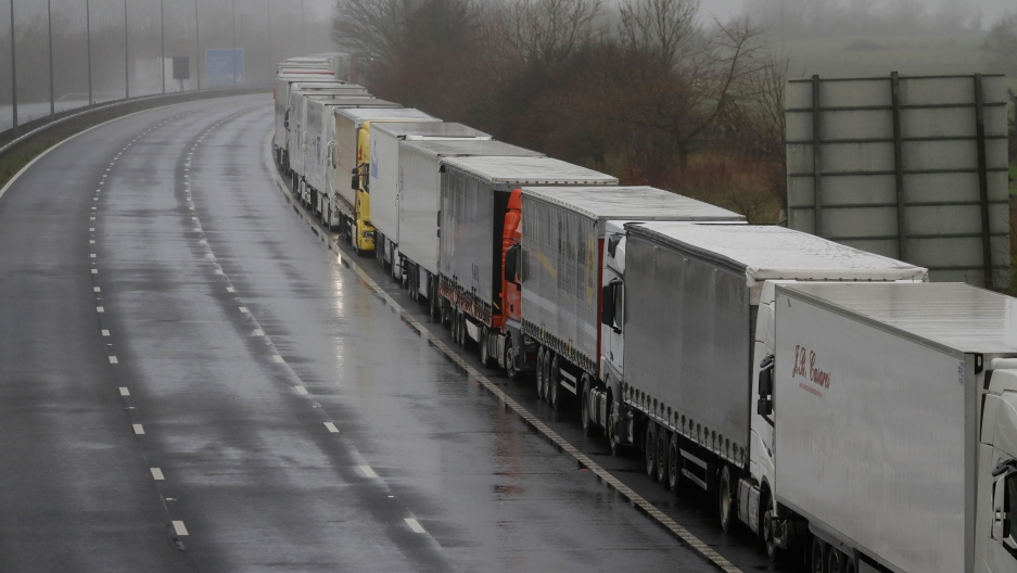 A long line of semi-trucks are shown bumper to bumper on a highway on an overcast day.