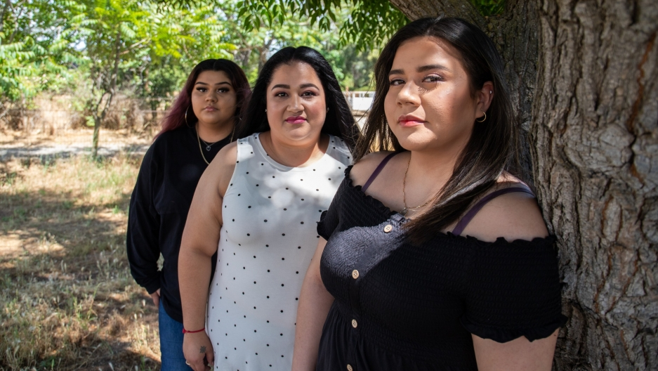 Three women related to each other stand together outside for a portrait wearing casual clothes and makeup.