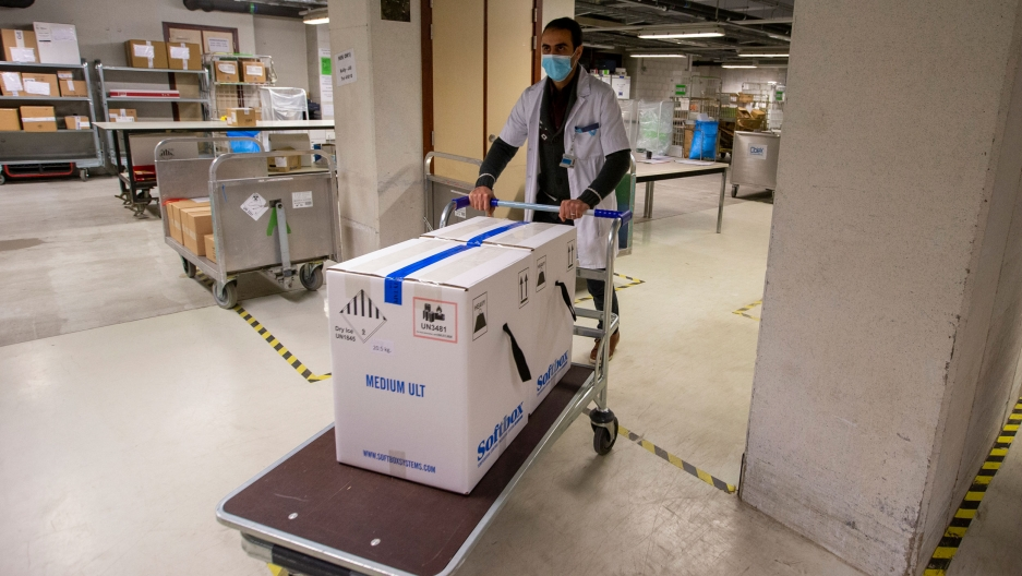 A man is shown wearing a white medical jacket and pushing a cart with two large white boxes on top sealed with blue tape.