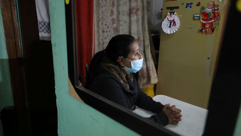 A woman is shown seated at a table with her hands crossed and wearing a face mask with a magnet of Santa Claus on the refrigerator in the background.