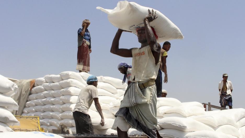 In this file photo, men deliver UNWorld Food Program (WFP) aid in Aslam, Hajjah, Yemen, Sept. 21, 2018.