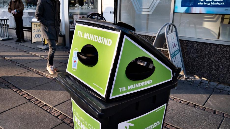 A green trash bin on a sidewalk in Denmark.