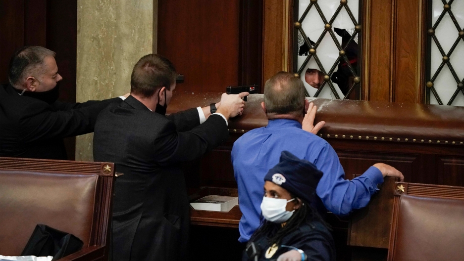 Police with guns drawn point at a rioter as a violent mob try to break into the House Chamber on Wednesday, Jan. 6, 2021, in Washington DC.