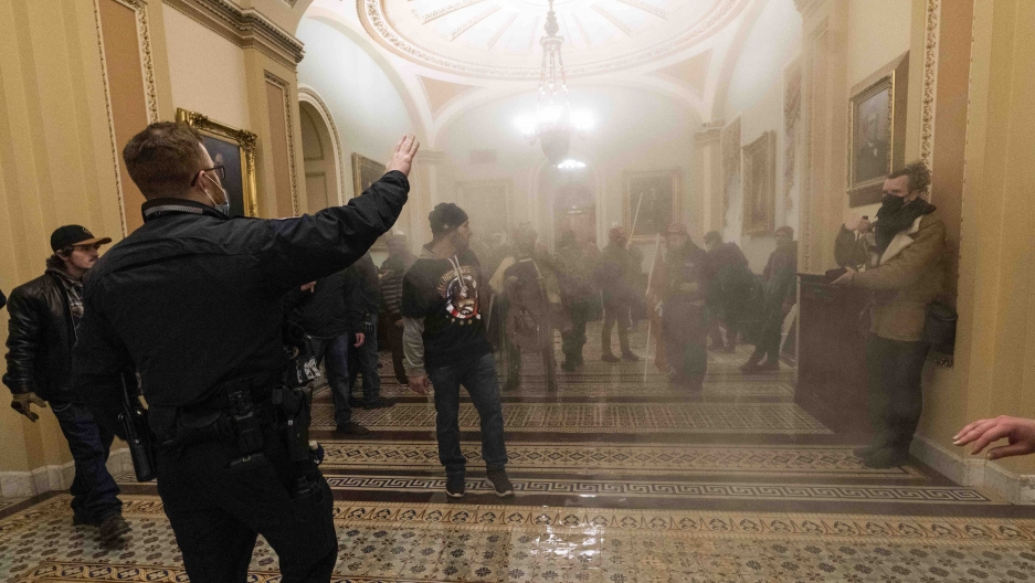 Smoke fills the walkway outside the Senate chamber as supporters of President Donald Trump are confronted by USCapitol Police officers inside the Capitol, Wednesday, Jan. 6, 2021, in Washington, DC.