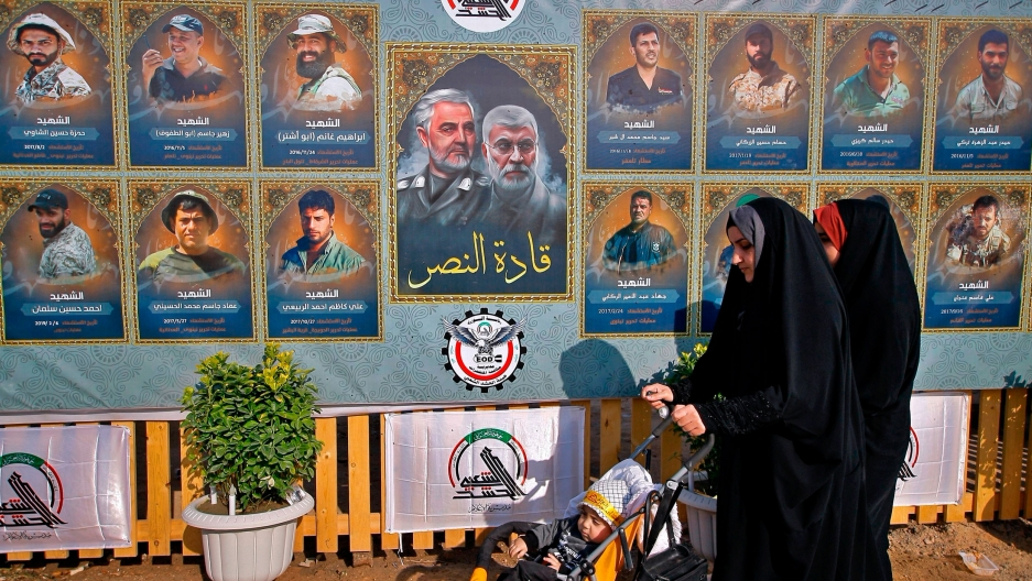 People pass by posters of Gen. Qassem Soleimani along with several other illustrated portraits alongside.