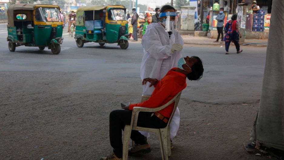 A man is shown sitting with his head back and a medical professional taking a nasal swab from his nose.