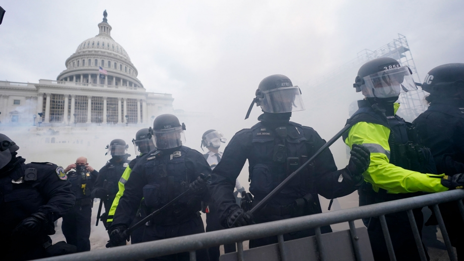 The US Capitol building is shown with smoke and riot police standing behind a baracade.