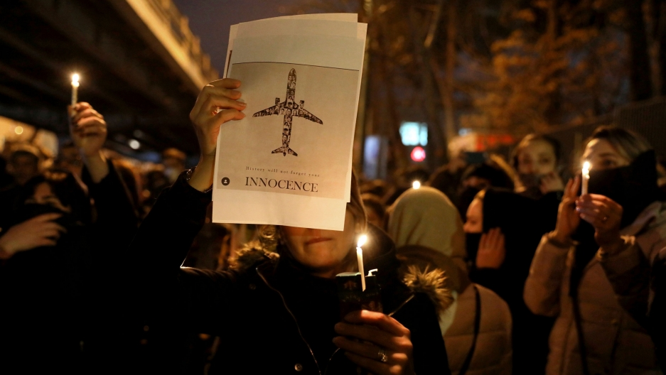 "A crowd of people are shown at night holding candles with one person holding a poster of an aircraft with the word ""Innocent"" printed on it."