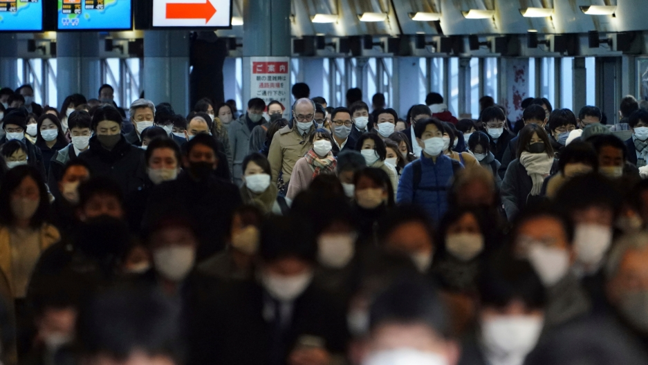 A station passageway is crowded with commuters wearing face mask during a rush hour Friday, Jan. 8, 2021, in Tokyo.
