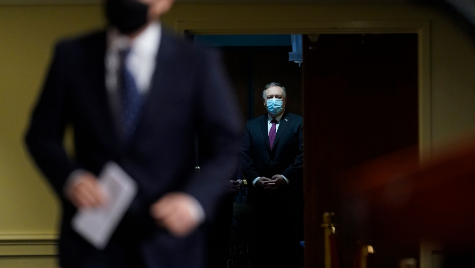 Secretary of State Mike Pompeo is shown in the distance framed by a doorway and wearing a suit with a face mask on.