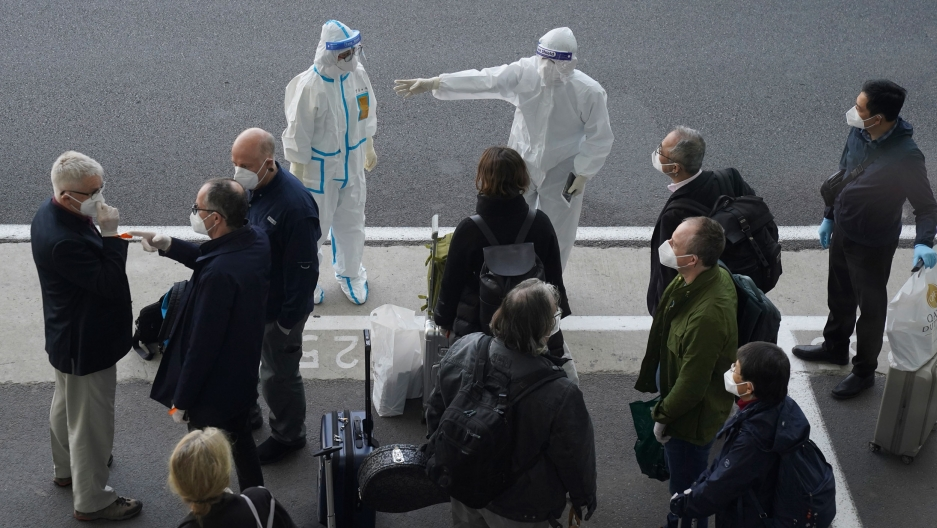 A small crowd of people are shown standing on a sidewalk with two people wearing white medical protective clothing and face masks.